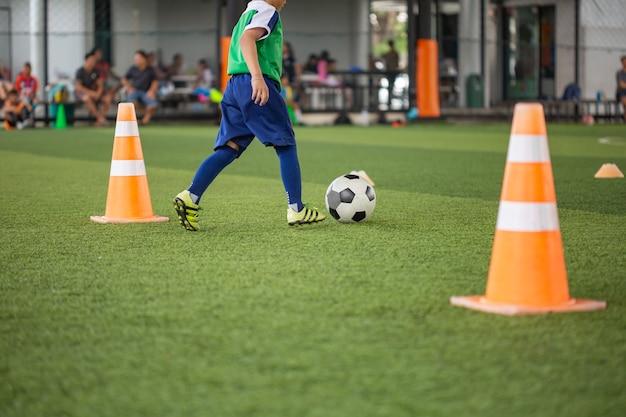 Táticas de bola de futebol no campo de grama com cone para treinar a tailândia em segundo plano. treinar crianças na academia de futebol