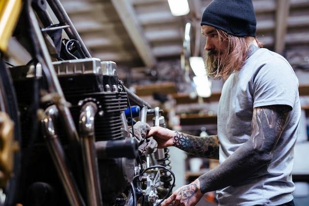 Tattooed biker fixing motorcycle in workshop