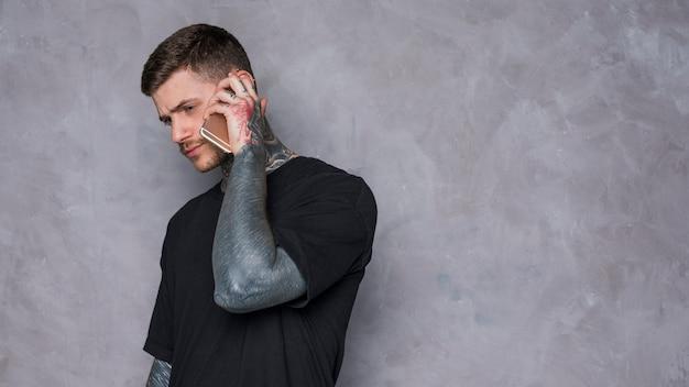 Tatuado jovem falando no celular contra o fundo da parede cinza texturizado