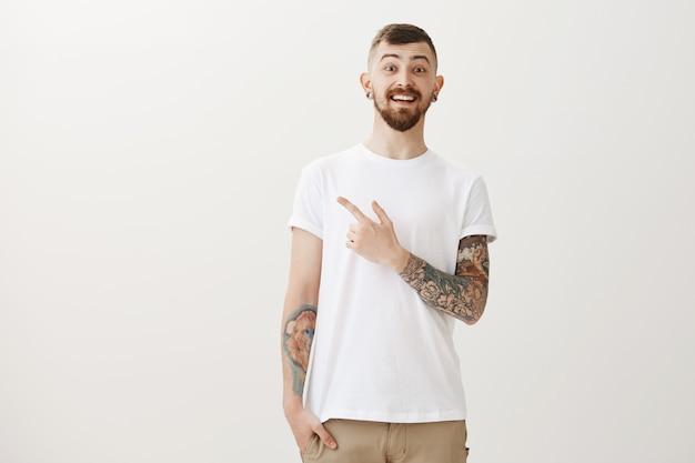 Tatuado lindo e entusiasmado apontando o dedo no canto superior esquerdo e sorrindo maravilhado