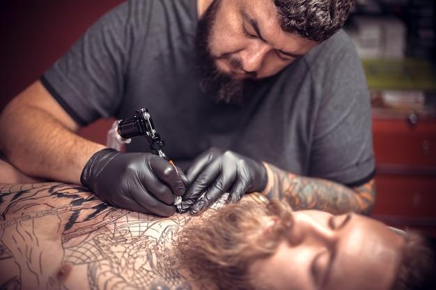 Tatuador faz tatuagens em um estúdio.