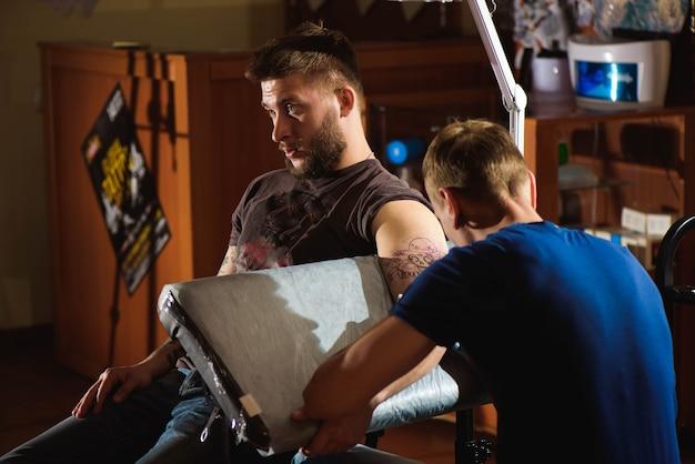Tatuador faz uma tatuagem. homem criando imagens por lado com ele no salão.