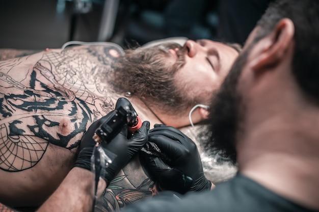 Tatuador focado em seu trabalho em estúdio de tatuagem.