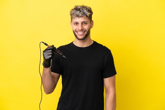 Tatuador homem caucasiano isolado em fundo amarelo, posando com os braços na cintura e sorrindo