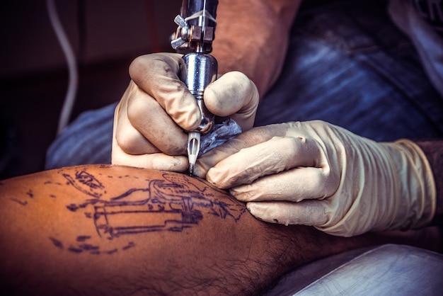 Tatuador no trabalho, close-up.