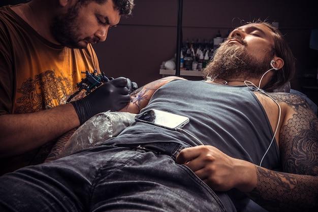 Tatuador posando no estúdio de tatuagem. / homem de luvas no trabalho no estúdio de tatuagem.