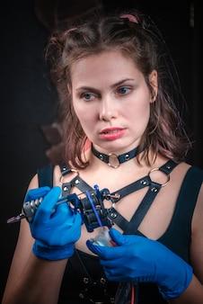 Tatuador profissional com máquina de tatuagem em estúdio de tatuagem.