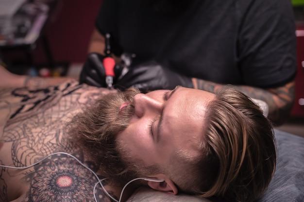 Tatuador profissional demonstra o processo de fazer uma tatuagem em seu salão.