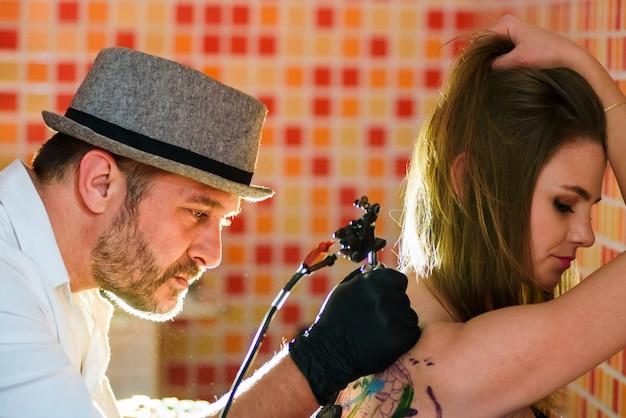 Tatuador profissional durante o processo de trabalho