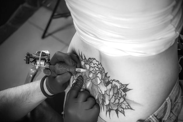 Tatuador profissional durante uma sessão de um tatuador em um estúdio de oficina.