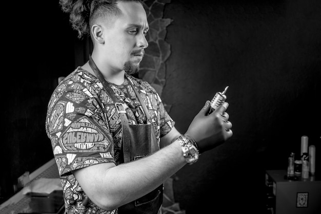 Tatuador profissional e uma pistola de tatuagem em um estúdio de tatuagem.
