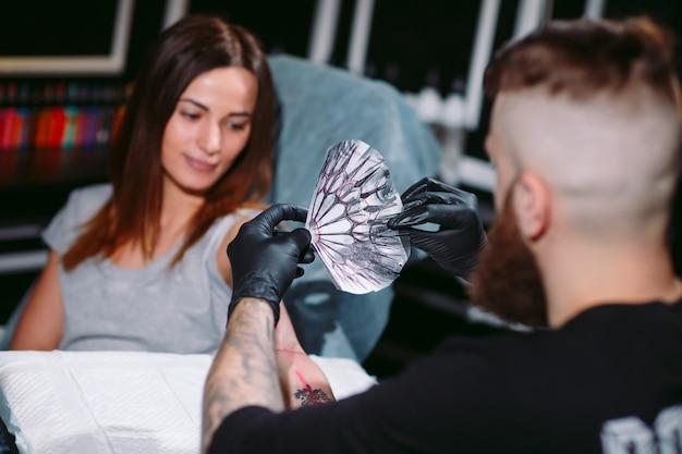 Tatuador profissional faz a tatuagem em uma garota.