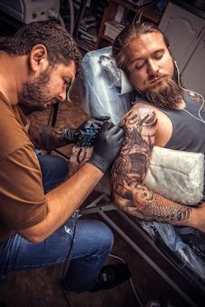 Tatuador profissional faz fotos de tatuagem em um estúdio de tatuagem