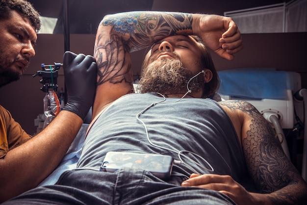 Tatuador profissional faz tatuagem legal no estúdio de tatuagem. / tatuador profissional faz tatuagem no estúdio de tatuagem.