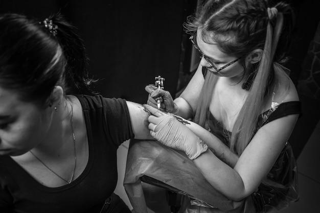 Tatuador profissional faz tatuagem na pele de seu cliente