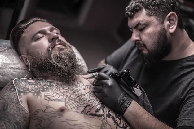 Tatuador profissional faz um estúdio de tatuagem de arte.