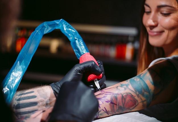 Tatuador profissional faz uma tatuagem na mão de uma jovem garota.