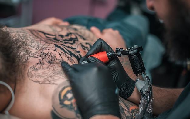 Tatuador profissional faz uma tatuagem na pele em um estúdio de oficina