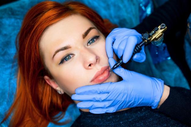 Tatuador profissional fazendo maquiagem permanente nos lábios para uma linda mulher ruiva.