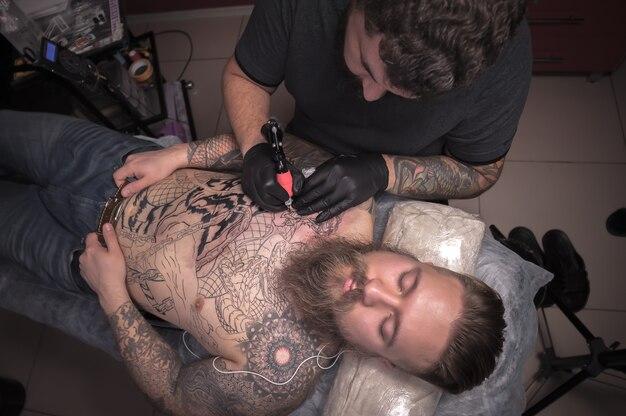 Tatuador profissional fazendo tatuagem em estúdio