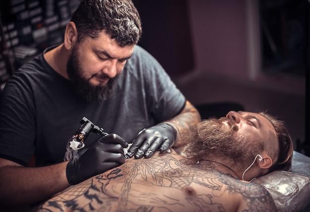 Tatuador profissional fazendo tatuagem no estúdio de tatuagem.