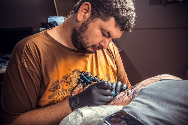 Tatuador profissional fazendo uma tatuagem em um estúdio de tatuagem