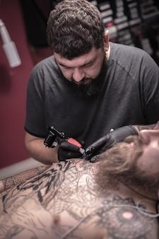 Tatuador profissional trabalhando em uma metralhadora profissional de tatuagem no salão