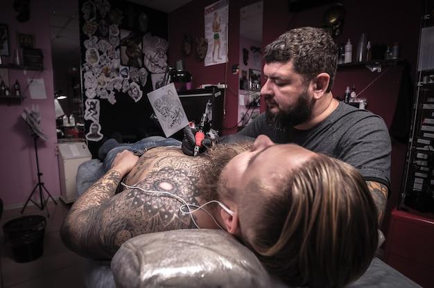 Tatuador profissional trabalhando em uma metralhadora profissional em um estúdio de tatuagem. / o tatuador faz uma tatuagem na pele em um estúdio de tatuagem.