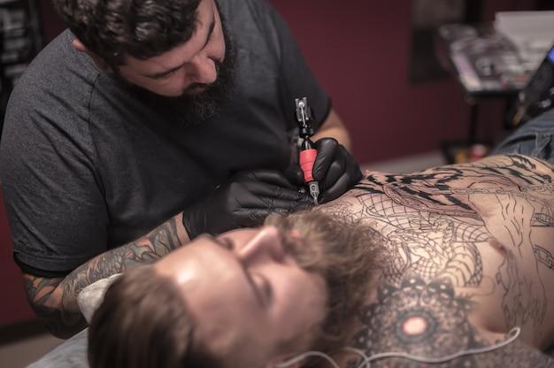 Tatuador trabalhando em um dispositivo de máquina de tatuagem profissional em estúdio.