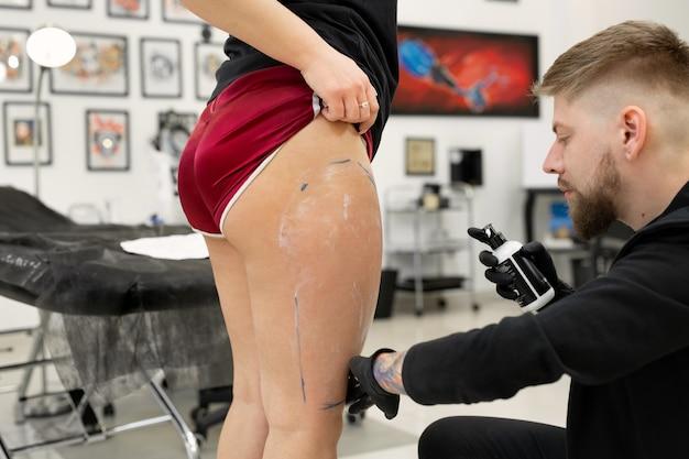 Tatuador transferindo um esboço de tatuagem para a perna de uma mulher em um estúdio de tatuagem