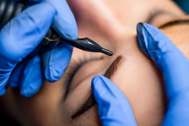 Tatuagem de maquiagem permanente nas sobrancelhas no salão de beleza. mulher com as sobrancelhas coloridas. maquiagem semi-permanente para sobrancelhas.