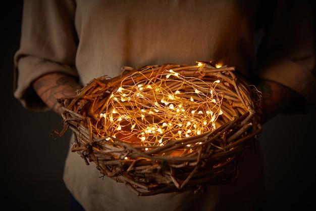 Tatuagem de mulher com as mãos segurando uma decoração de ninho com luzes