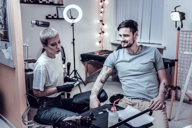 Tatuagem enorme. cliente bonito sorridente do sexo masculino relaxando na poltrona enquanto o mestre trabalha com sua tatuagem especiosa
