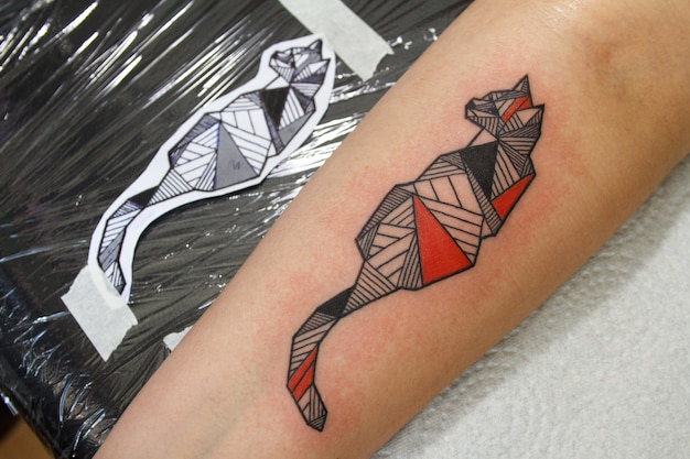 Tatuagem fresca de close-up no braço do cliente ao lado de um desenho de tatuagem, pele avermelhada do trabalho da máquina de tatuagem