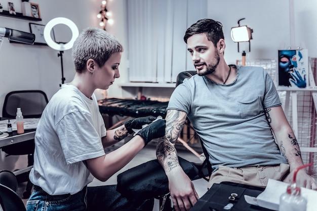 Tatuagem ilusória. uma tatuadora concentrada coberta por tatuagens criando sombras para seu cliente regular