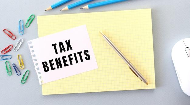 Tax benefits é escrito em um pedaço de papel que fica em um caderno ao lado de materiais de escritório. conceito de negócios.