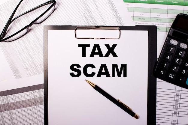 Tax scam é escrito em uma folha de papel branca, perto dos óculos e da calculadora.