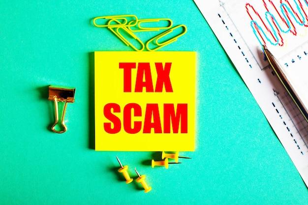 Tax scam está escrito em vermelho em um adesivo amarelo em uma mesa verde perto do gráfico e do lápis