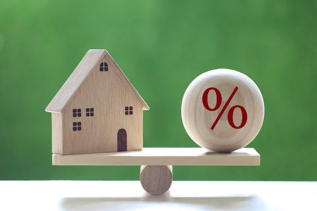 Taxa de juros alta e conceito bancário, casa modelo com ícone do símbolo de porcentagem na gangorra de escala de madeira em fundo verde natural, taxa fixa