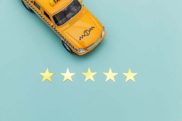 Táxi de carro de brinquedo amarelo e classificação de 5 estrelas isolada em fundo azul. aplicação por telefone do serviço de táxi para pesquisa on-line, chamando e reservando o conceito de táxi. símbolo de táxi copie o espaço.