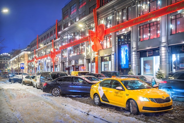 Táxi e carros amarelos na frente da loja de departamento central em moscou e decoração na fachada da loja em forma de um laço vermelho à luz das luzes da noite legenda: feliz ano novo!