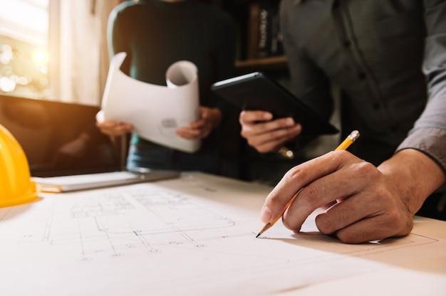 Tcarquiteto criativo projetando grandes desenhos no escritório escuro do loft ou no café à luz da manhã