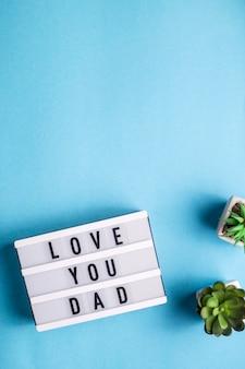Te amo pai está escrito em uma lâmpada decorativa sobre um fundo azul