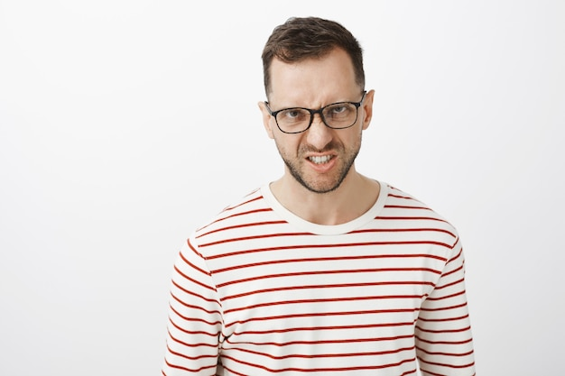Te odeio de todo coração. retrato de um europeu indignado de óculos escuros, olhando por baixo da testa e franzindo a testa, mostrando os dentes de raiva