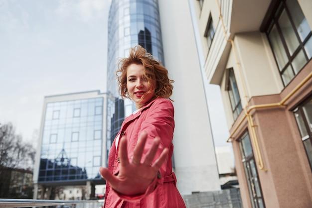 Te vejo em breve. mulher adulta bonita com casaco vermelho quente passeando pela cidade nos fins de semana