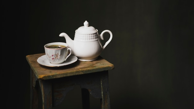 Teapot e chávena no tamborete