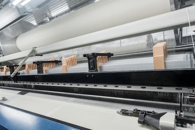 Tear de tecelagem em uma fábrica de têxteis, closeup. linha de produção de tecido industrial