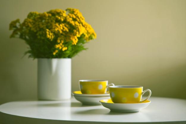 Teaset vintage - duas xícaras retrô pontilhadas amarelas e flores de crisântemo amarelas na mesa branca.