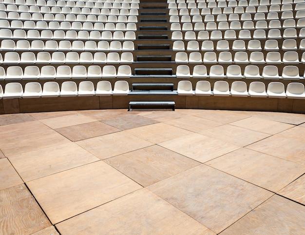 Teatro ao ar livre com luz natural; fileiras de assento de plástico