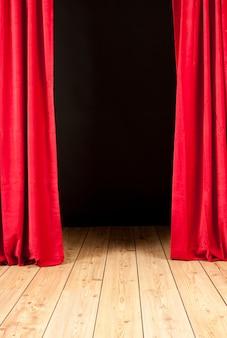 Teatro de palco com cortina vermelha e piso de madeira